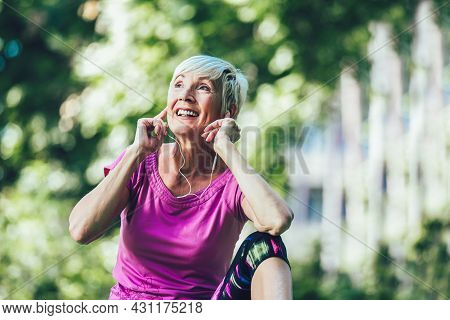 Senior Woman Exercising In Park While Listening To Music. Mature Woman Resting After Exercise.