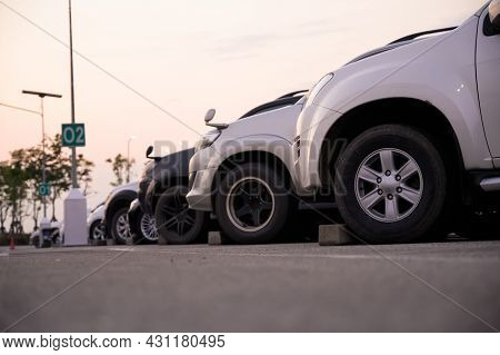 Many Cars Are Parked In A Large Parking Lot. Arranged In A Long Line Was The Time When The Sun Was S