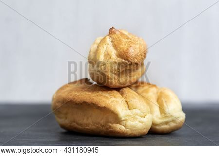 Delicate Profiteroles Or Eclairs Without Cream. Close Up. White Background