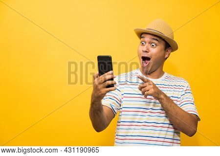 Asian Man Happy With His Smartphone On Yellow Background. Young Man Using Looking At Smartphone.