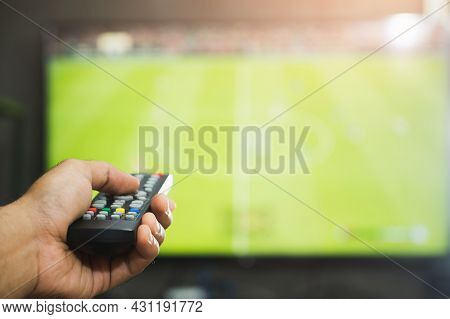 Young Man Holding Television Remote Control Watching Football Program. Hands Pointing To Tv Screen S