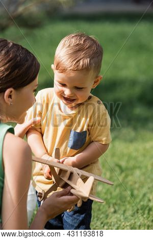 Blurred Cheerful Mother Near Smiling Toddler Boy With Wooden Biplane