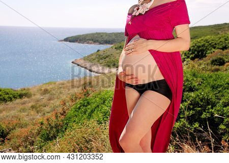 Beautiful Pregnant Woman And Lady Is Hugging And Holding Her Pregnant Belly, Standing In Natural Env