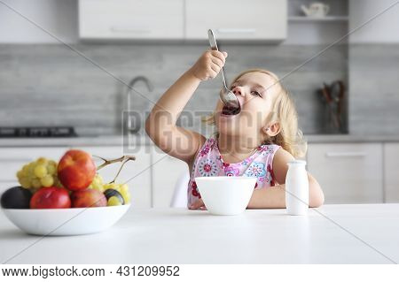 Little Caucasian Girl Enjoing Food Sitting At Table Indoors. Child Have A Meal. Organic Breakfast, H