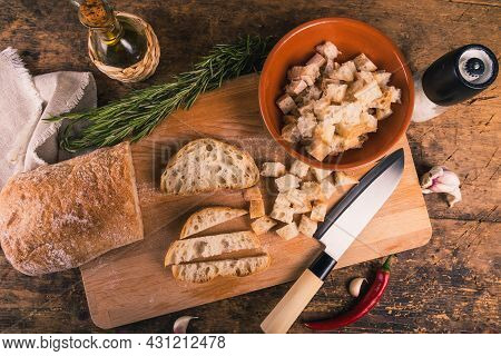 Making Ciabatta Garlic And Rosemary Croutons - Ciabatta And Diced Bread Cubes On A Board And In A Bo