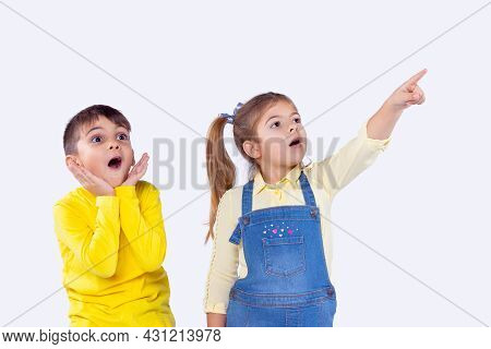 Cheerful Girl And Boy Being Excited Staring Up Pointing To Something Incredible They See.