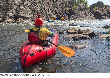 A Woman Rowing Inflatable Packraft On Whitewater Of Mountain River. Concept: Summer Extreme Water Sp