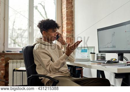 Irritated Young Male Trader Talking On The Phone Discussing Stock Market While Looking At Charts, Tr