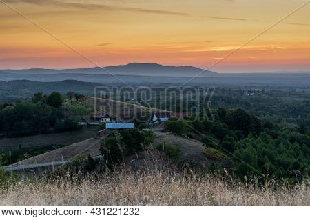 Hilly Countryside Landscape With Farmhouse, Meadows, Forests And Distant Mountain In Haze, Beautiful