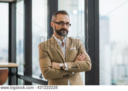 Young Handsome Business Bearded Man Standing Near Window With Arms Crossed In Office Work Place.