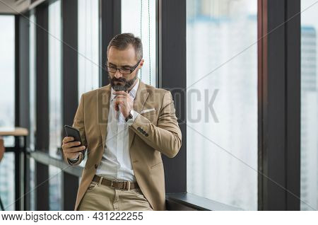 Young Handsome Business Bearded Man Standing Post Near Window Using Smartphone In Office Work Place.