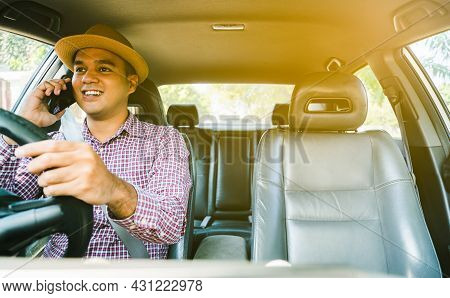 Young Asian Man Using Smartphone While Driving Car