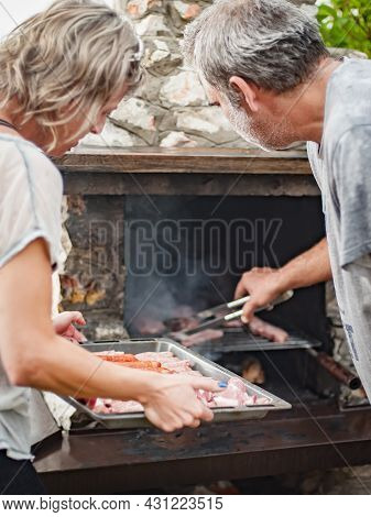 Bbq Grilling Party. Couple In Garden Making Barbecue Grill