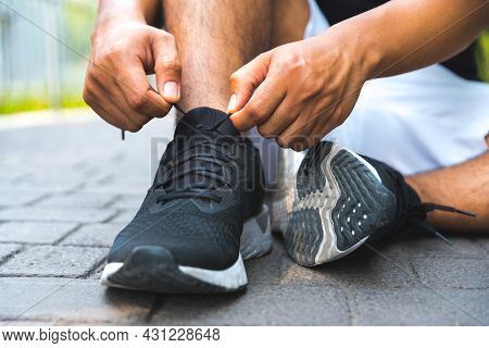 Sport Concept. Close Up Running Man Tying Shoelaces