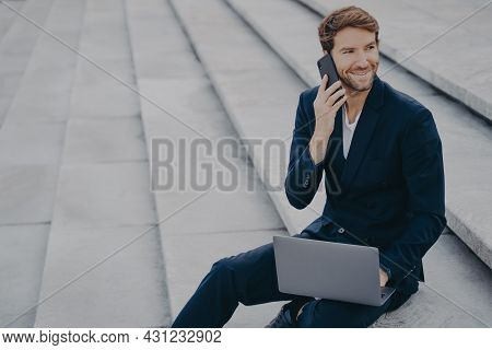 Caucasian Satisfied Man In Formal Outfit Sitting On Steps Outdoor, Talking On Mobile Phone And Worki