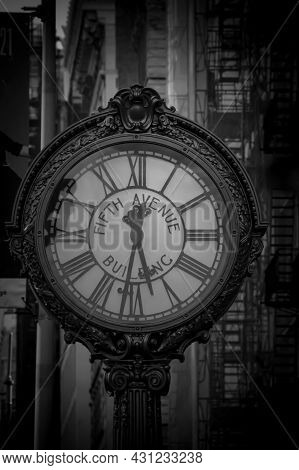 Grayscale Photo Of The Fifth Avenue Building Street Clock Near Buildings With Fire Escapes On A Blur