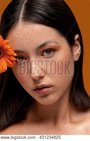 Natural Beautiful Woman With Freckles Holding A Flower In Hand Near Face. Girl With Fashionable Make