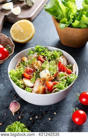 Caesar Salad With Smoked Chicken And Parmesan On A Plate On Dark Background