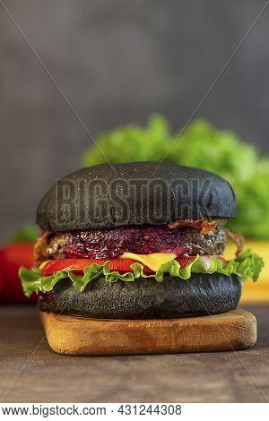 Black Burger. Fresh Tasty Black Burger On A Black Background. Close-up. Copy Space