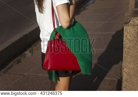 Woman Walking With Pullover Hanging On Her Handbag, Sunny Day Shot