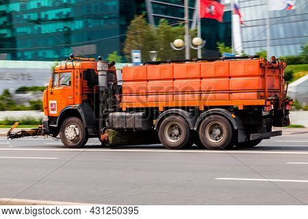 Orange Water Jetting Truck Is Riding On The Street. Water Carrier Car Going To Wash The Asphalt Road