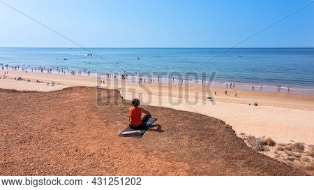 A Middle-aged Woman, During A Vacation In Portugal, Sits On A Rug On A Cliff, In Front Of The Sea An
