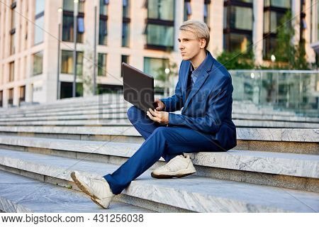 White Collar With Laptop Sits Near Office Building.