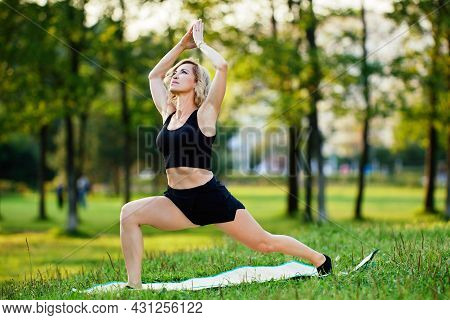 Active Woman In Shorts Trains Yoga Outdoors.