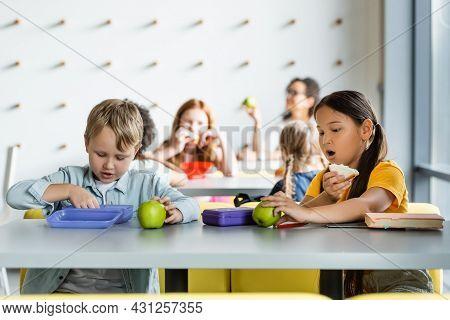 Asian Schoolgirl Eating Sandwich Near Classmates During Lunch Break