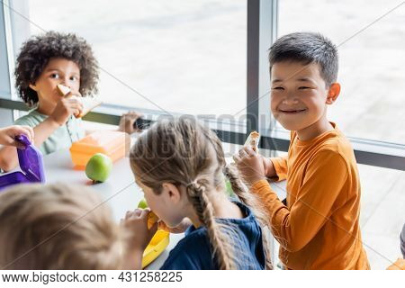Asian Boy Smiling At Camera During Lunch With Multiethnic Classmates