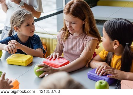 Redhead Girl Holding Apple And Opening Lunch Box Near Multiethnic Classmates