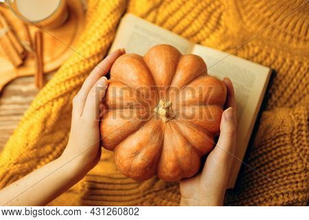 Round Ripe Pumpkin In Hands, Hot Latte, Open Romantic Book And Warm Knitted Sweater. Autumn Composit