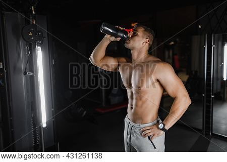 Bodybuilder In The Gym. Muscular Man In Gym With Shaker. Strong Male Abs, Bodybuilding Concept Backg