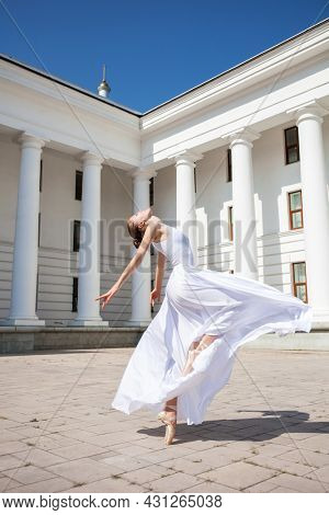 Dancer in a long white skirt dancing on the background of the theater