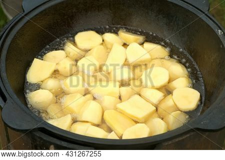 Potato Is Frying In Cauldron In Oil On Nature On Fire, Closeup View. Preparing Food On Campfire In C