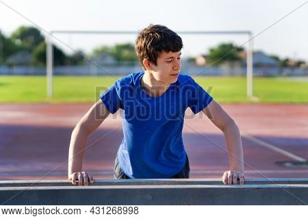 a guy on the edge of the stadium field does a push-ups, healthy lifestyle