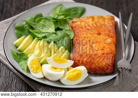 Oven Baked Salmon Fillet With Creamy Ripe Avocado, Baby Spinach And Hard Boiled Eggs On A Plate On A