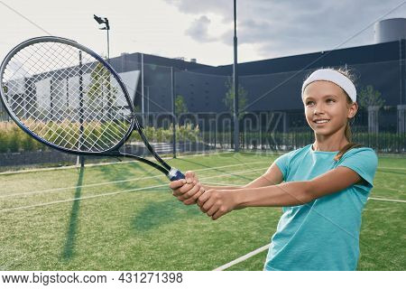 Beautiful Child In Sportswear With Tennis Racket While Playing Tennis On Tennis Court. Little Girl T