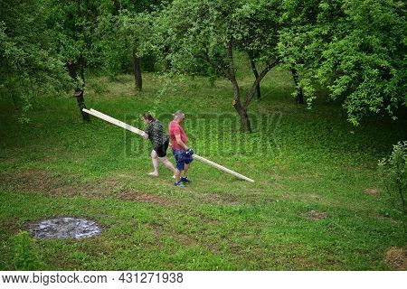 People Carry Wood In The Garden With Trees Near The Cottage
