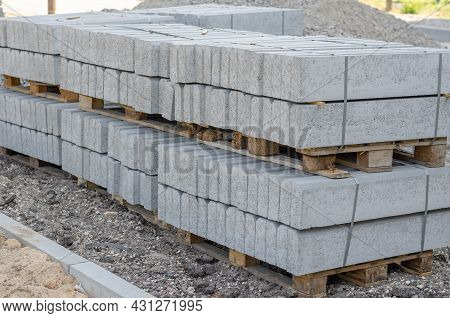 A Stack Of New Gray Boarders Stacked On Pallets. Concrete Road Barriers Strapped Together. Repair An
