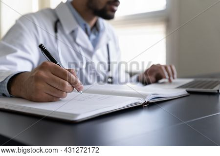 Close Up Cropped Young African American Male Doctor Handwriting Notes.