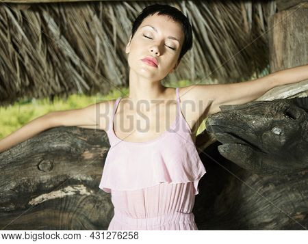 Beautiful lady pose in exotic shouth location. Sexy lady in pink dress