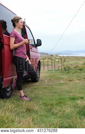 Woman Resting With A Cup In Her Hand Next To Her Campervan On Her Summer Holiday.