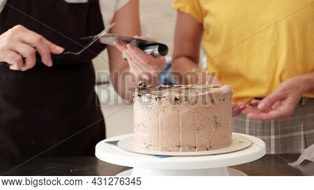 4k Woman Pastry Chef Smooths Chocolate Cream On Chocolate Cake, Close-up. Slow Motion. Cake Making M