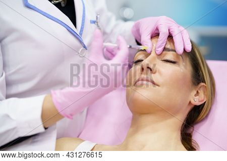 Aesthetic Doctor Injecting Botulinum Toxin Into The Forehead Of Her Middle-aged Patient.