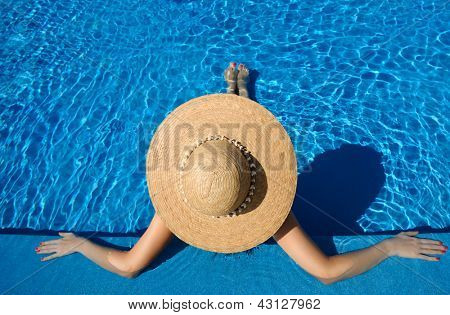Woman in hat relaxing at the pool