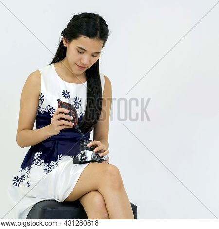 Young Asian Photographer In Blue Dress Cleaning The Camera Lens With Air Blower.