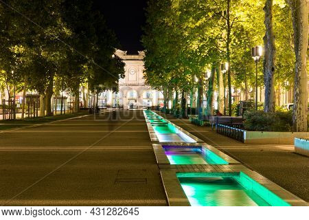 Avenue Feucheres At Night With Illuminated Stream-like Fountain In Nimes, France