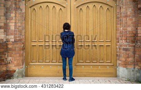 A Woman Is Facing The Huge Gate Of A Catholic Church Trying To Open The Door.