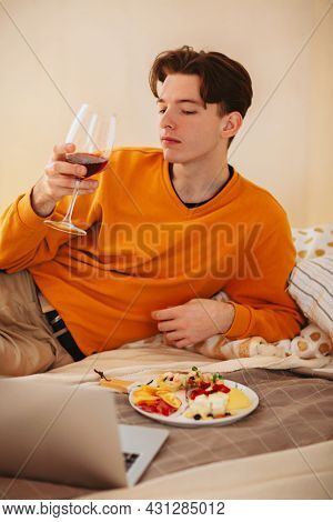 Relaxed Young Guy With Glass Of Wine In His Hands Laying On Comfortable Bed With Plate Of Food, Watc